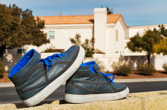 Gray Shoes on the fence. Gray Shoes with blue laces up on the fence Stock Image