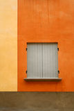 Gray shutters. Orange plaster and gray shutters Royalty Free Stock Images