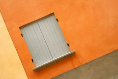 Gray shutters. Orange plaster and gray shutters Stock Photo