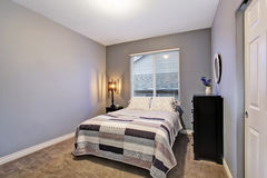 Gray simple bedroom with big bed, large window. Royalty Free Stock Photography