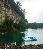 People in Tubes in a Lake on a Natural Rock Quarry. Gray skies and clouds as people are swimming to shore in tubes in the lake. Little girl is climbing up the stock photo