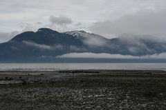 Gray Skies in Southeastern Alaska Landscape. Typical cloudy weather and gray skies with mist and fog in Southeastern Alaska landscape of beach and island stock photos