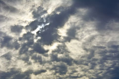 Gray sky with clouds with translucent rays of the sun. Royalty Free Stock Images