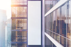 Gray skyscraper exterior, side, toned. Side view of an exterior of a gray skyscraper with large windows and a gigantic poster between them. 3d rendering, mock up Stock Image