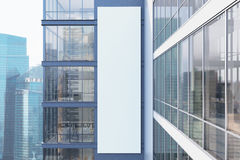 Gray skyscraper exterior, side. Side view of an exterior of a gray skyscraper with large windows and a gigantic poster between them. 3d rendering, mock up Royalty Free Stock Photos
