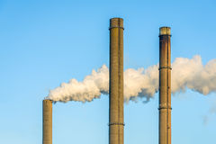 Gray smoke from a high chimney against a blue sky. Gray and dirty smoke from a high concrete chimney of a power station contrasting with a bright blue sky on a royalty free stock image