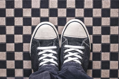 Gray Sneakers on Checkered Pattern Pavement, Top View. Overhead Shot of Man Standing on Street, Urban Lifestyle Concept Stock Photo