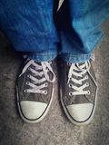Gray sneakers. And denim jeans with white shoelaces Royalty Free Stock Images