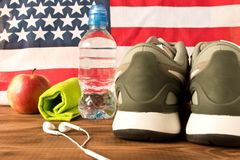 Gray sneakers and fitness accessories on the background of the American flag. The concept of the health of the nation. Selective stock image