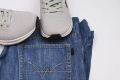 Gray sneakers and jeans. Clothing for walking. Clothing for travel. Sport shoes and blue jeans. Men`s shoes on a white background stock photos