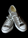 Gray sneakers youth footwear at black background Royalty Free Stock Photography