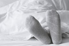 Gray socks relaxing on the white bed. Foot in gray socks relaxing on the white bed royalty free stock photos