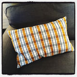 Gray sofa with checked cushion Stock Images