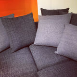 Gray sofa with lots of cushions Stock Image