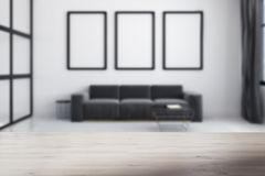 Gray sofa, poster gallery blurred. White living room interior with a long sofa standing under three framed posters on a carpet on a concrete floor. Blurred. 3d Stock Photos