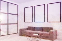 Gray sofa, poster gallery side toned. White living room corner with a long sofa standing under three framed posters on a carpet on a concrete floor. 3d rendering Royalty Free Stock Images