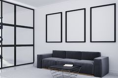 Gray sofa, poster gallery side. White living room corner with a long sofa standing under three framed posters on a carpet on a concrete floor. 3d rendering mock Royalty Free Stock Photography
