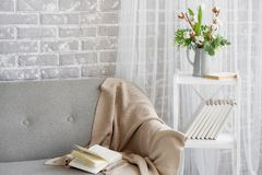 On the gray sofa there is a beige plaid trimmed with lace.