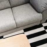 Gray sofa and wooden coffee table Stock Photos