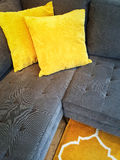 Gray sofa with yellow cushions Stock Images
