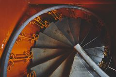 Gray spiral staircase in an old orange train, in ocher style,  spirals and descending lines of steps. Gray spiral staircase in an old orange train, in ocher royalty free stock photos