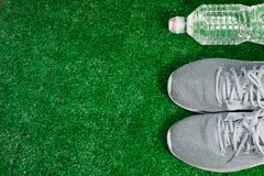 Gray Sports Running Shoes and bottle of water on green grass. Sport and relax concept stock image