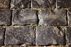 Gray square cobblestones close-up. The stone surface of the road. The road of stones and cobblestones.  royalty free stock photography