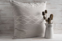 Gray Square Throw Pillow Beside Thistle Plants in Vase. A gray square throw pillow, with white concave line pattern design, next to decorative dried thistle Royalty Free Stock Image