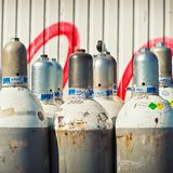 Gray Steel Gas Tanks Near White Steel Wall during Daytime Stock Photos
