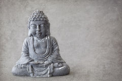 Gray stone buddha. On a gray background royalty free stock photography