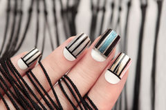 Gray striped nail design . Gray striped nail design on female hand close up Stock Photo