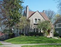 Gray Stucco House con los árboles y las flores de la primavera Imagenes de archivo