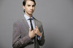 Gray suit. Handsome young confident guy in gray suit Stock Photography