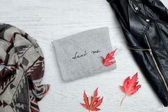 Gray sweater with the inscription, a black jacket, scarf and autumn leaves. Fashionable concept.  Stock Photo