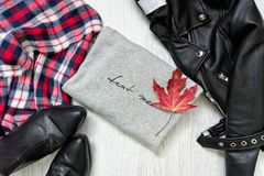 Gray sweater and maple leaf. Black jacket, checkered scarf and boots. Fashionable concept Royalty Free Stock Photography