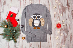 Gray sweater with an owl on a wooden background. Fur-tree branch with Christmas decorations Stock Image