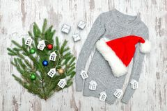 Gray sweater, Santa`s hat and fir branch on a wooden background. Gifts and small houses Stock Images