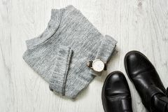 Gray sweater, watch and black boots. Fashionable concept, top view.  Stock Image