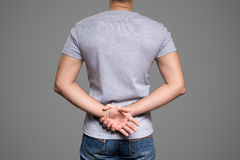 Gray t-shirt on a young man template. Back view. Gray background Stock Image