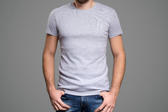 Gray t-shirt on a young man template. Gray background. Royalty Free Stock Photo