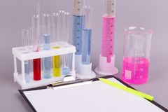 Closeup of test tubes on a gray background, near the tablet with a blank sheet and pen. stock photos