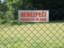 Gray tag hanging on the fence. Gray tag hanging on the wire mesh fence with the red inscription in the Czech language (translation: risk of being bitten by a stock photo