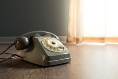 Gray telephone on hardwood floor. Gray vintage table on hardwood floor next to a window Royalty Free Stock Photos
