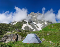 Gray tent in grass on background of mountains and rocks Stock Images