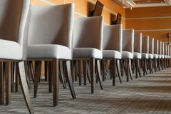 Gray textile chairs with brown wooden legs stand in a straight l stock image