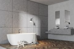 Gray tile bathroom corner, white tub. Luxury gray bathroom interior idea. A wooden floor, a double sink and a white bathtub. Large gray tiled walls. A side view Royalty Free Stock Photos