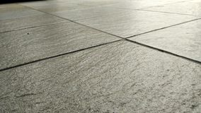 Gray tile floors background. Gray tile floors in closeup, great for background and texture editing stock images