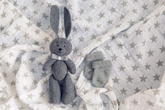 Gray toy rabbit lies Stock Images