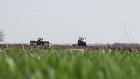 Gray tractor go on black earth field. Two gray tractor with planter and plow go on black earth field in spring under the high-voltage wires from not focus stock video footage