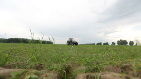 Gray tractor rides on the green field Royalty Free Stock Photos